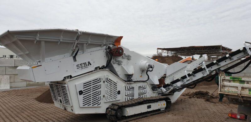 Photo du Crible Mobile Compact 2 étages 2.5m² SEBA S25-10 - Châssis chenilles, vidant les matériaux criblés dans un camion benne 3T5