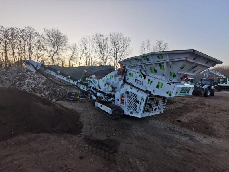 Vue arrière du Crible Mobile Compact 2 étages 2.5m² SEBA S25-10 - Châssis chenilles, dans une carrière avec différents matériaux comme de la terre, des gravats, du béton, du calcaire