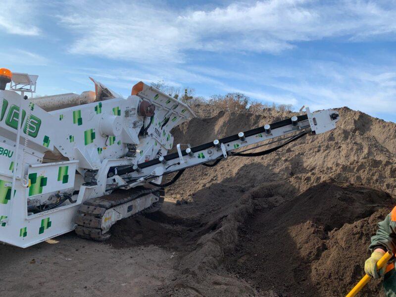 Dans une carrière, le Crible Mobile Compact 2 étages 2.5m² SEBA S25-10 - Châssis chenilles, renvoie les matériaux triés très fin formant un tas de terre