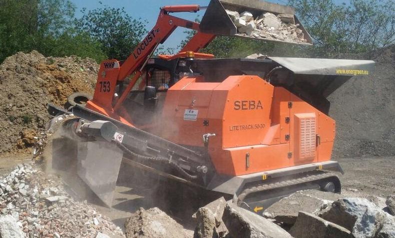 Chargeuse déposant des gravats de béton et calcaire dans le Concasseur Mobile Compact SEBA LITE TRACK 50-30 sur chenilles qui sort des gravats concassés après la sortie du tapis