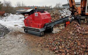 Concasseur Mobile Compact SEBA LITE TRACK 50-30 sous la neige dans une carrière devant un tas de gravats d'argile