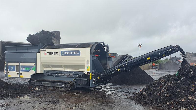 Cribles Trommels Terex Ecotec TTS 518T en fonctionnement avec un tas de déchets après la sortie du convoyeur de la machine